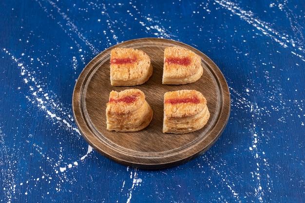 De savoureux gâteaux en tranches avec de la confiture placés sur une planche de bois