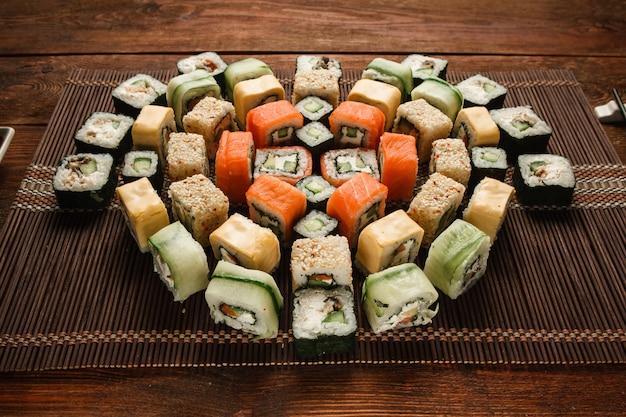 Savoureux grand ensemble coloré de rouleaux de sushi maki japonais frais servis sur un tapis de paille marron, gros plan. art culinaire, fruits de mer traditionnels, photo de menu de restaurant de luxe.