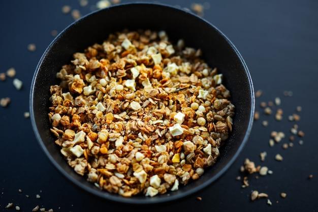 Savoureux granola muesli fruité maison servi dans un bol sur fond sombre. fermer
