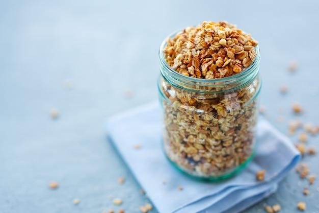 Savoureux granola muesli fruité maison en verre sur fond clair. fermer