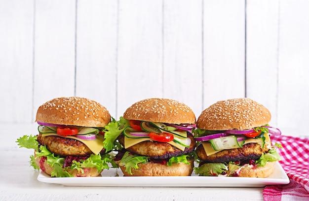 Savoureux hamburger maison grillé avec poulet burger, tomates, fromage, concombre, laitue et betterave.