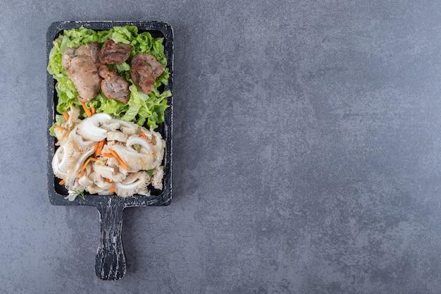 Savoureux kebab grillé et salade de légumes sur planche de bois.