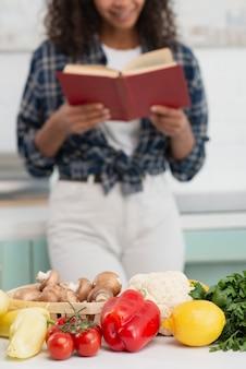 Savoureux légumes avec une femme lisant en arrière-plan