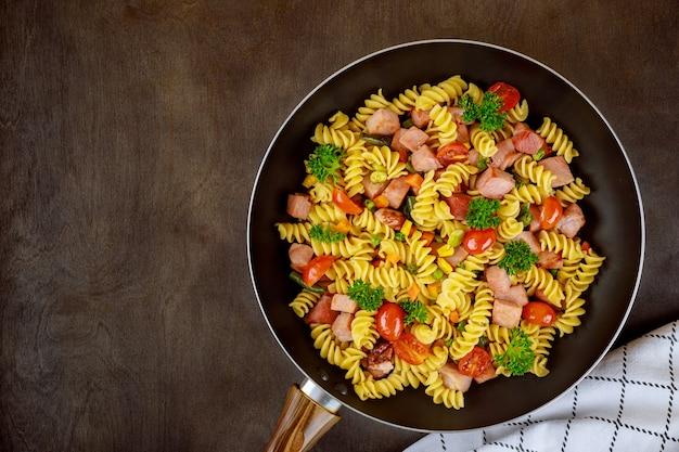 Savoureux macaronis aux légumes et jambon de porc coupé.