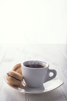 Savoureux macarons sucrés et tasse à café. macarons sur un fond en bois blanc. espace de copie