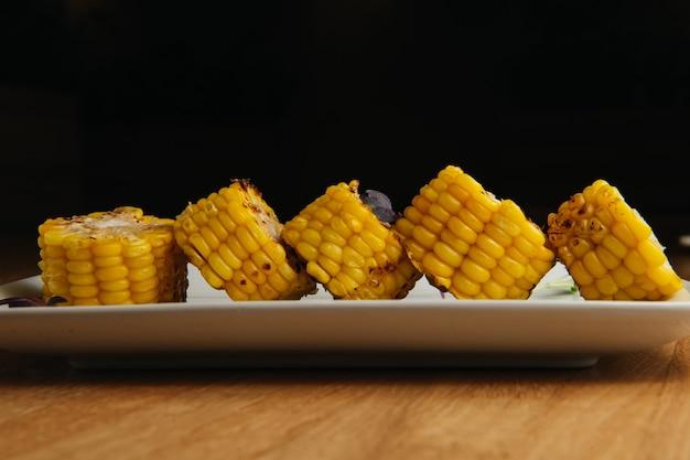 Savoureux maïs grillé sucré sur plaque blanche. nourriture d'été