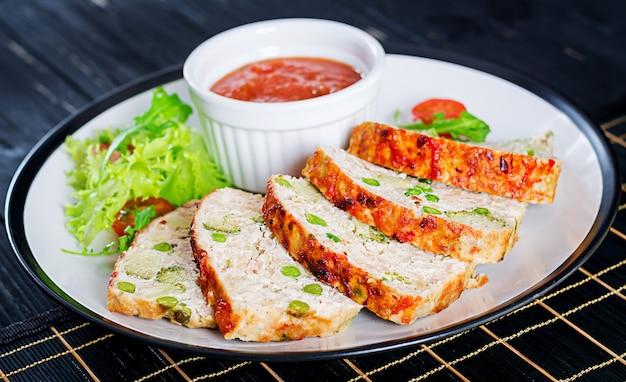 Savoureux pain de viande haché fait maison au poulet, aux pois verts et au brocoli sur un tableau noir.