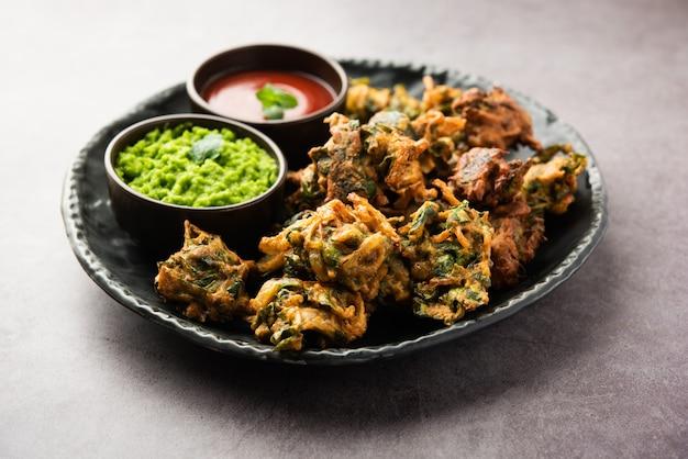 Savoureux palak pakoda ou pakora fait maison, connu sous le nom de firtters aux épinards, servi avec du ketchup. collation préférée à l'heure du thé en inde