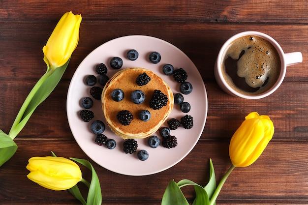 Savoureux petit-déjeuner avec des crêpes et du café frais sur fond de bois rustique fleurs de tulipe humeur de printemps
