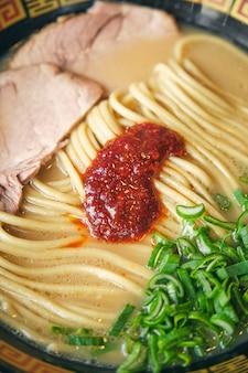 Savoureux ramen avec salsa de tomates sur nouilles en bouillon