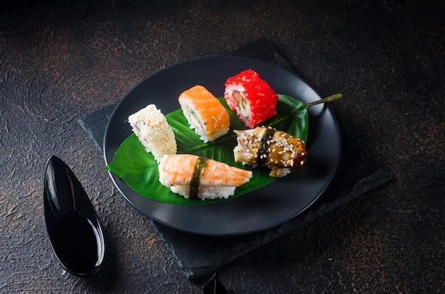 De savoureux rouleaux de sushi sur une plaque noire avec des sauces, des baguettes, du gingembre et du wasabi sur une table sombre. carte de sushis. service de livraison de plats japonais. assortiment de sushis, petits pains, gunkans, nigiri.