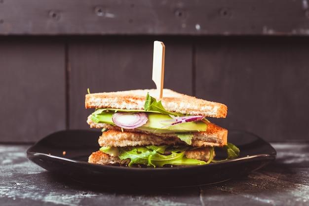 Savoureux sandwich végétalien avec avocat et salade sur une assiette sombre
