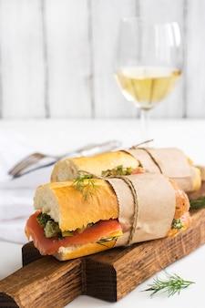 Savoureux sandwiches au saumon fumé sur table blanche