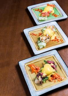 Savoureux sandwichs du matin avec légumes, fromage et viande dans des assiettes sur une table en bois