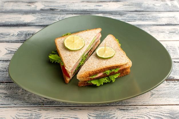 Savoureux sandwichs à l'intérieur de la plaque verte sur fond gris