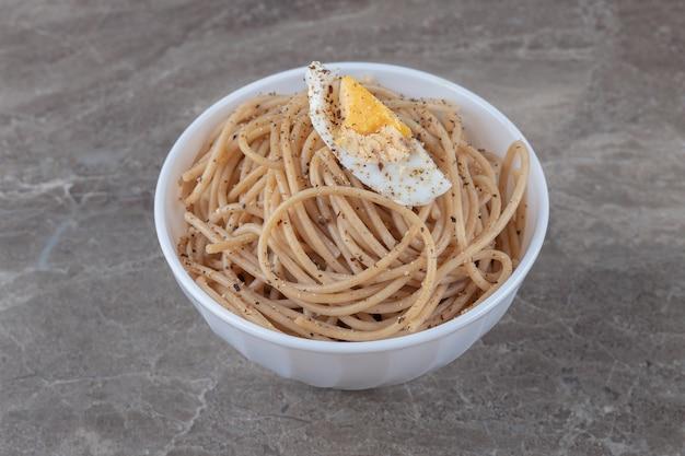 De savoureux spaghettis aux œufs dans un bol blanc.