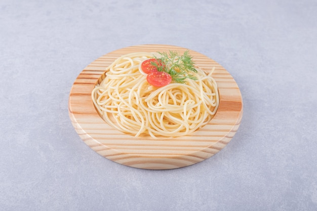 De savoureux spaghettis bouillis aux tomates sur une plaque en bois.