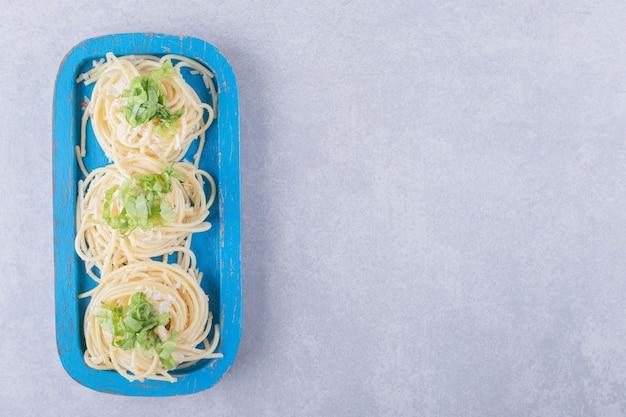 De savoureux spaghettis bouillis avec des verts sur une plaque bleue.
