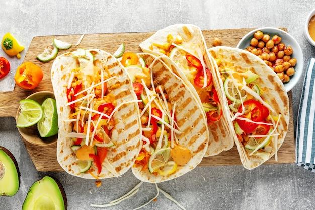 De savoureux tacos végétaliens frais faits maison avec des pois chiches et des légumes servis à bord. vue de dessus.