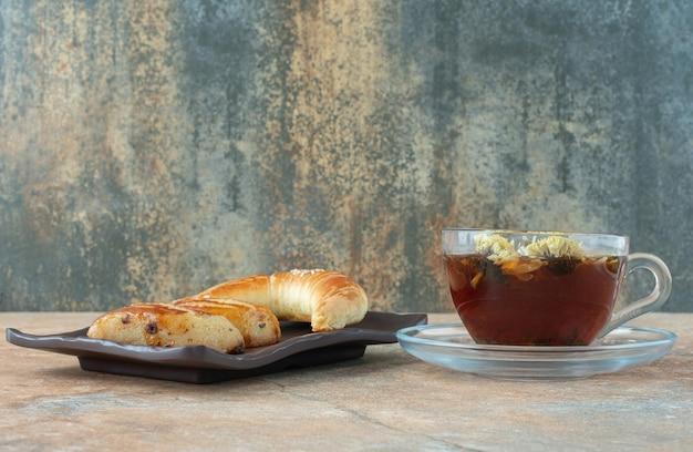 Savoureux thé à la camomille avec des biscuits sur table en marbre.