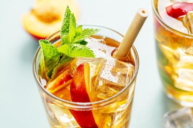 Savoureux thé glacé fraîchement préparé avec de la pêche, de la menthe et des glaçons. servi dans des verres avec de la paille de bambou.