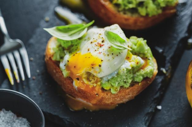 Savoureux toasts appétissants avec avocat et œuf servis sur une planche sombre.