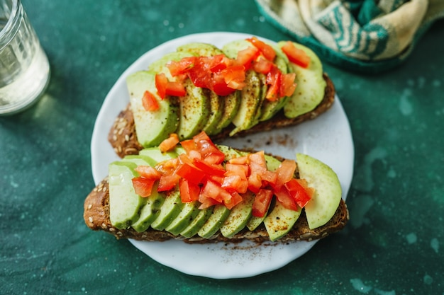 Savoureux toasts appétissants avec avocat et tomates servis sur assiette.