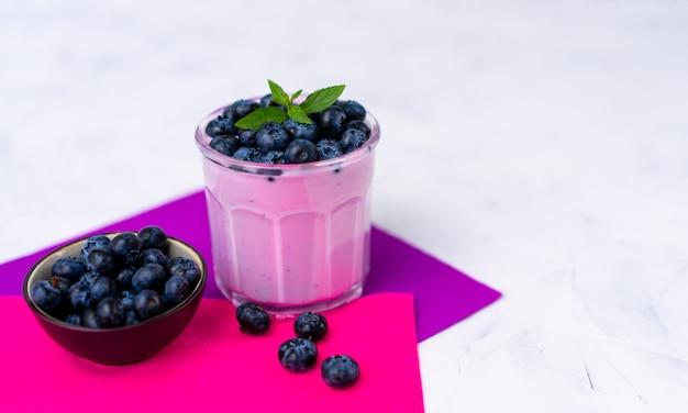Savoureux yaourt aux myrtilles fraîches shake dessert en verre debout sur la serviette de table violet blanc. smoothie aux fruits fait maison. alimentation équilibrée. yaourt diététique