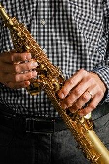 Saxophone soprano en mains sur fond noir