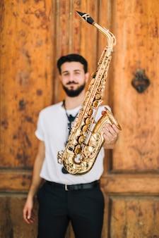Saxophone tenu par un musicien défocalisé