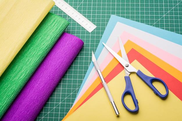 Scalpel, ciseaux, règle, papiers de couleur, papier ondulé sur tapis de découpe