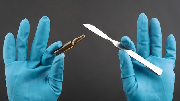 Scalpel médical et flacon pour injection dans les mains avec des gants bleus. traitement des malades