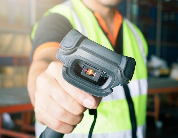 Scanner de code à barres de numérisation de travailleur closeup dans l'entrepôt.