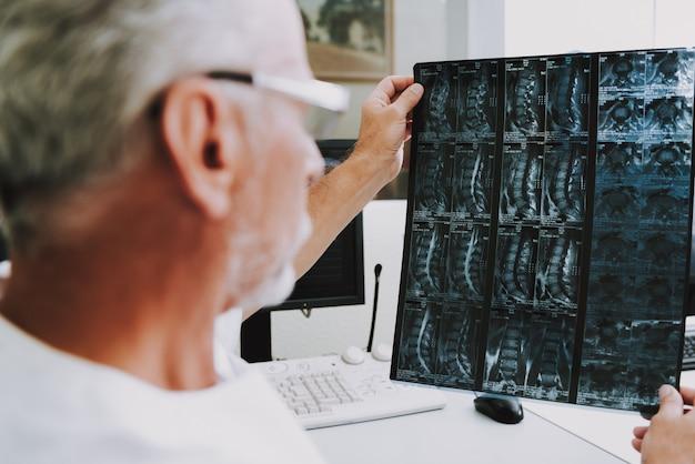 Scanner de tomodensitomètre professionnel de personnes âgées examinant.