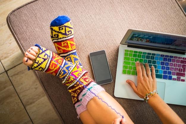 Scène d'accueil colorée avec des jambes de femme de race blanche avec des chaussettes colorées amusantes avec un trou pour que les pieds sortent