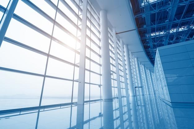Scène d'aéroport moderne de mouvement de passagers flou avec fenêtre à l'extérieur.