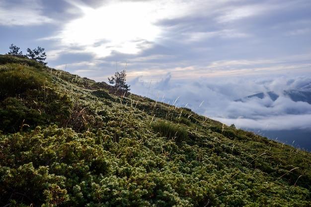 Scène automnale de haute montagne avec nuages bas menaçant la pluie.