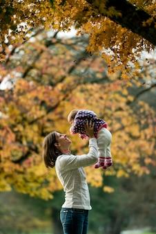 Scène d'automne de la mère joyeuse jouant avec le jeune bébé sous l'arbre.