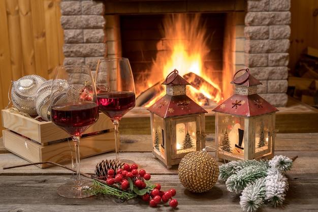 Scène chaleureuse devant la cheminée avec des verres de vin et des décorations de noël