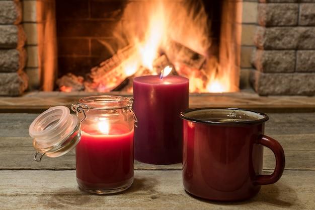 Scène chaleureuse près de la cheminée avec une tasse de thé chaud, un foulard chaud et des bougies.