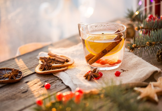 Scène confortable devant la cheminée et l'arbre de noël décoré de jouets et de lumières de noël avec des tasses de thé sur une table en bois, dans une maison de campagne, vacances d'hiver du soir de noël.