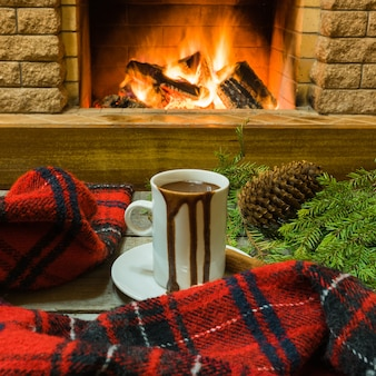 Scène confortable devant la cheminée avec une tasse de chocolat chaud, une écharpe chaude et des décorations de noël.
