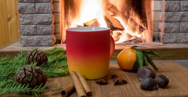 Scène confortable près de la cheminée avec une tasse de boisson chaude, de la tangarine, des cônes, des noix et du pain à la cannelle.