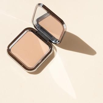 Scène cosmétique moderne minimale avec de la poudre, conciliateur sur fond nude