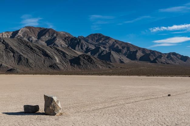 Scène du désert avec une longue trace laissée par deux pierres sur le sol sec et des collines à l'arrière