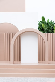 Scène d'espace vide minimal avec mur peint en rose, arc, escalier rose et cactus artificiel
