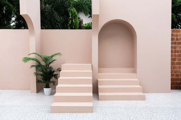 Scène d'espace vide minimal avec mur peint en rose et petite marche avec arc