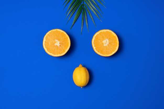 Scène d'été avec feuille de palmier tropical, orange et citron sur fond bleu. esthétique minimale. style plat. copier l'espace