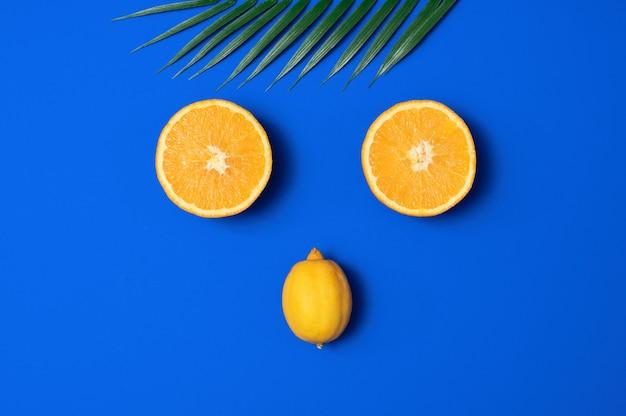 Scène d'été avec feuille de palmier tropical, orange et citron sur fond bleu.