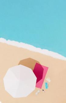 Scène d'été sur la plage avec serviette et parasol avec masque protecteur, gants, désinfectant pour les mains et lunettes de soleil